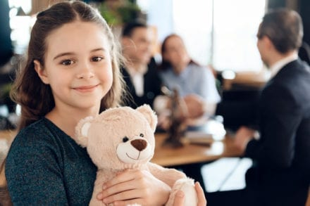 girl smiling holding a bear stuffed animal