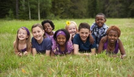 kids from different ethnicities smiling laying on the grass