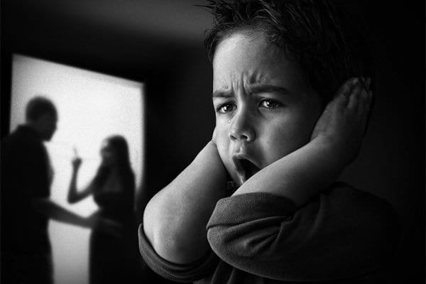 Young boy covering his ears to avoid hearing domestic violence