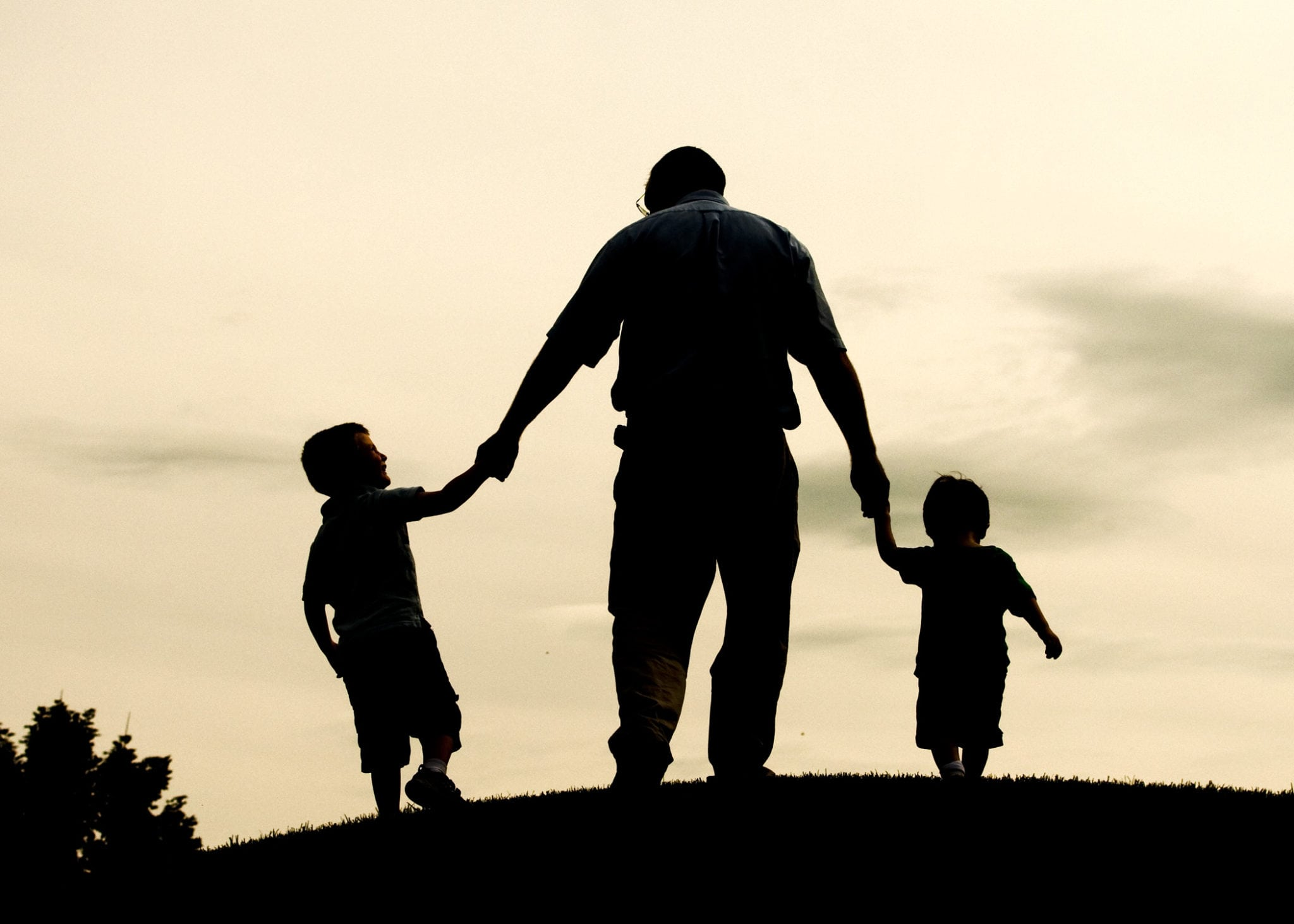 Father on a hill with 2 children