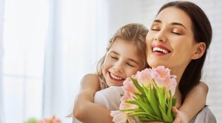 Mother and daughter hugging holding pink flowers