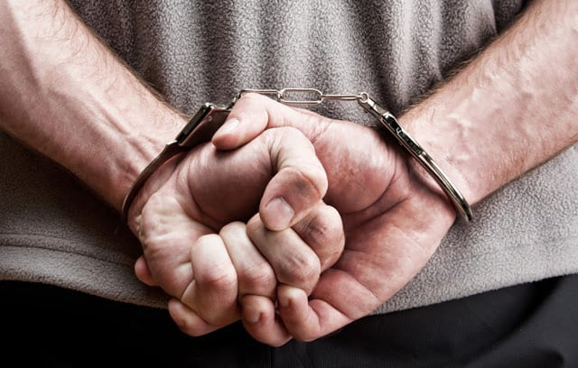 A man with his hands handcuffed behind his back