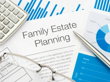The image shows glasses, and pen and a calculator accompanied by Estate Planning documents.