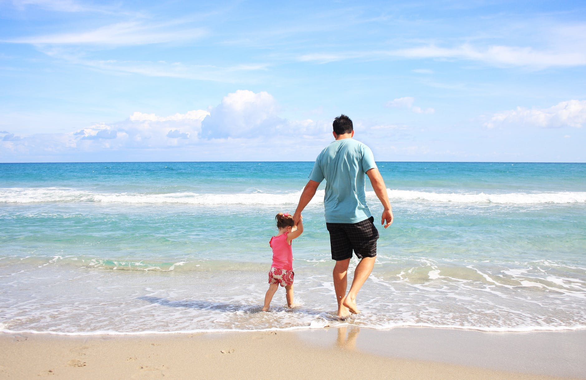 father and kid walking on the beach holding hands