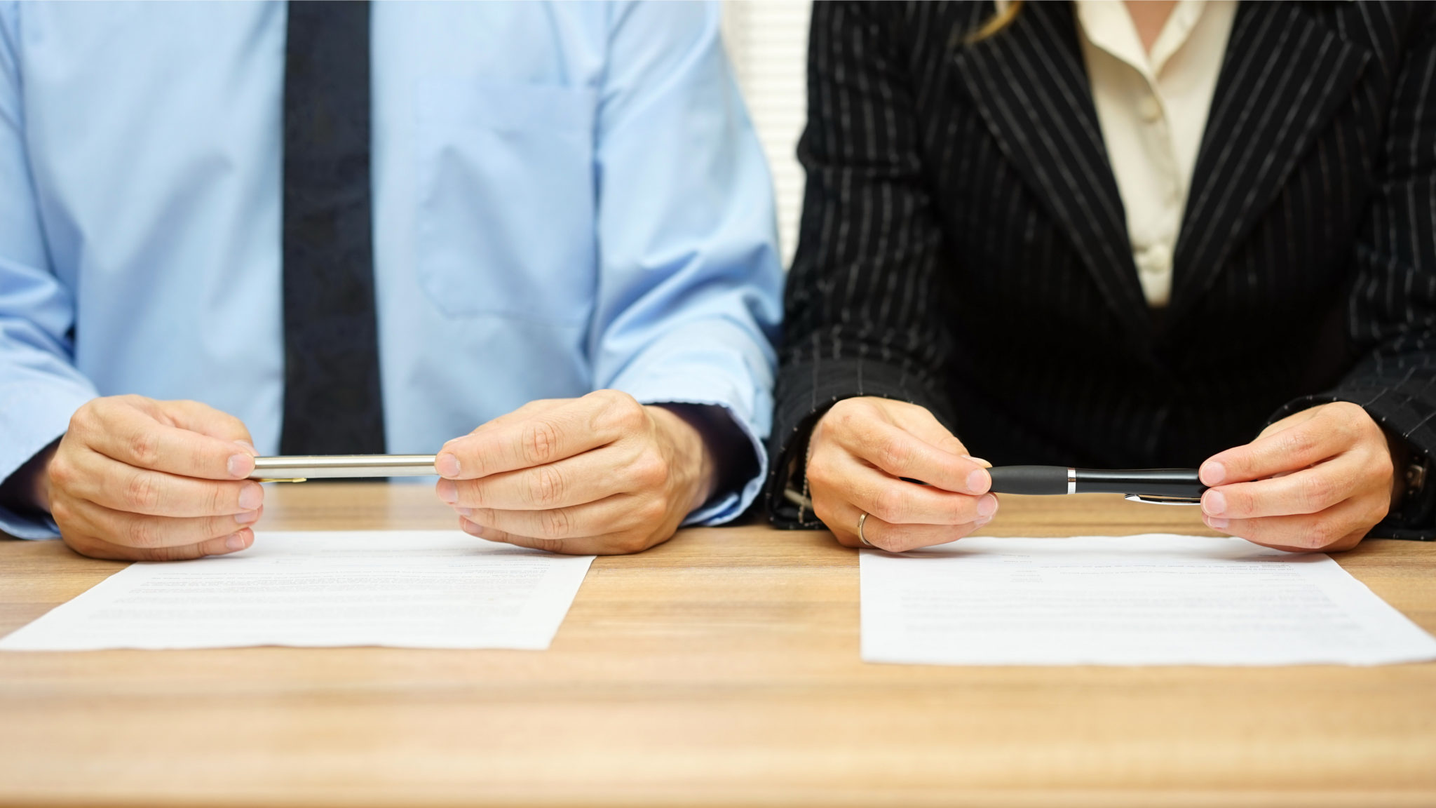 man and woman holding a pen in front of a divorce contract