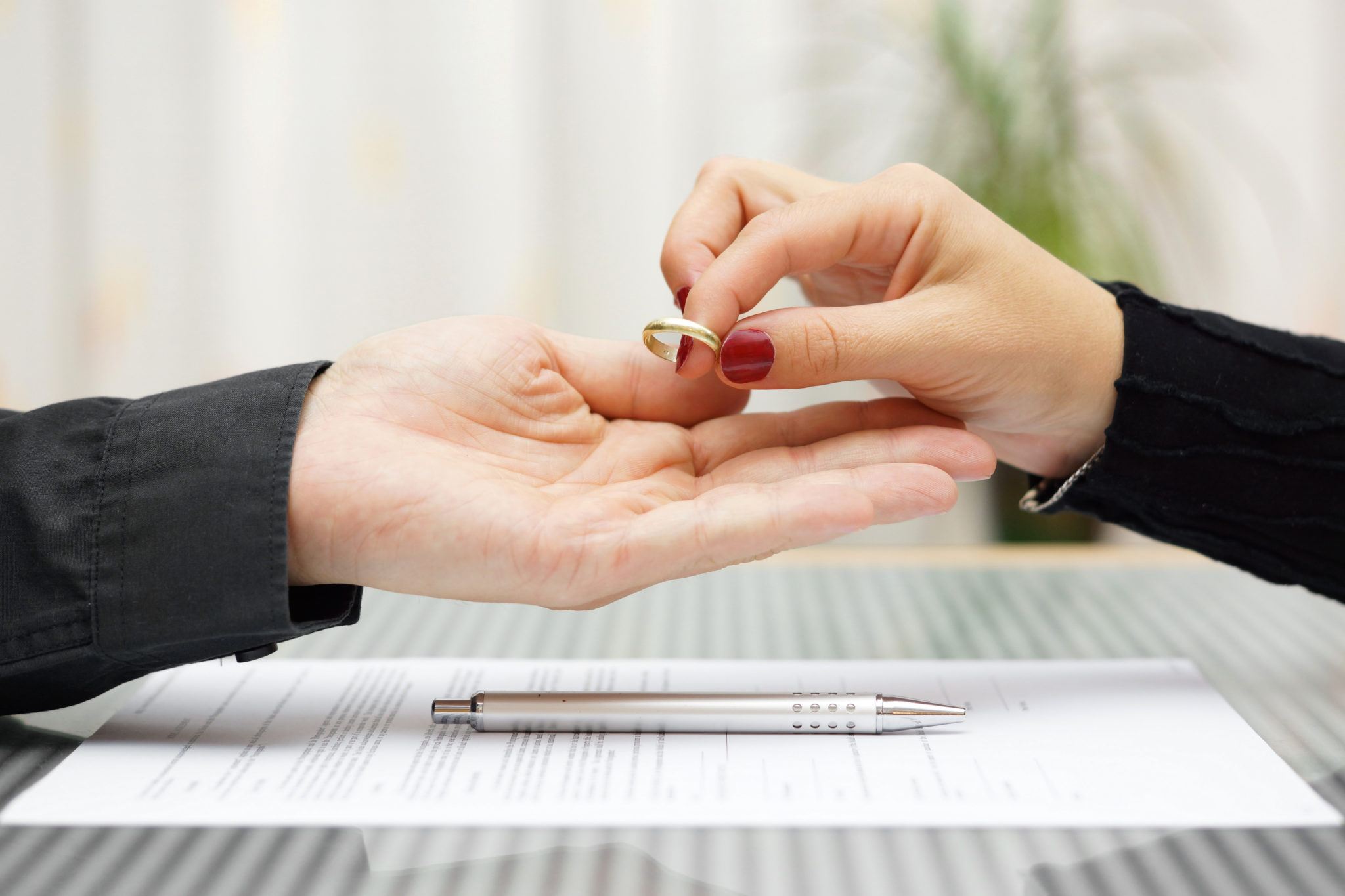 woman handing wedding to a man divorce contract and pen